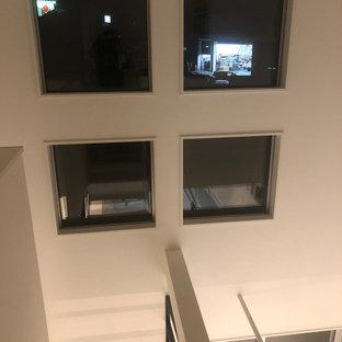 Ejemplo de escalera en U y papel pintado, moderna, de tamaño medio, sin contrahuella, con escalones de madera, barandilla de metal y papel pintado