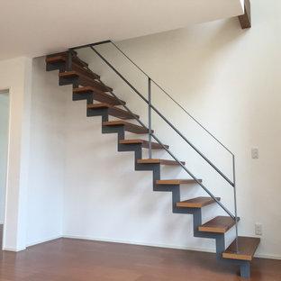 Bild på en liten funkis trappa i trä, med öppna sättsteg och räcke i metall
