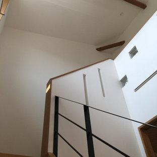 Ejemplo de escalera en L y papel pintado, moderna, de tamaño medio, con escalones de madera, contrahuellas de madera pintada, barandilla de metal y papel pintado