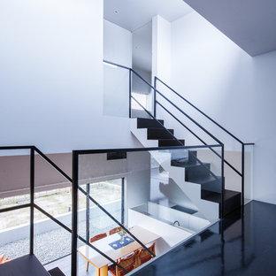 他の地域のコンテンポラリースタイルのおしゃれな折り返し階段 (金属の手すり) の写真