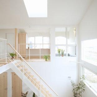 Foto de escalera recta, nórdica, de tamaño medio, con escalones de madera, contrahuellas de madera y barandilla de metal