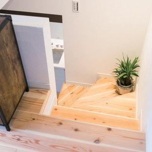 Ejemplo de escalera curva y papel pintado, campestre, sin contrahuella, con escalones de madera, barandilla de metal y papel pintado