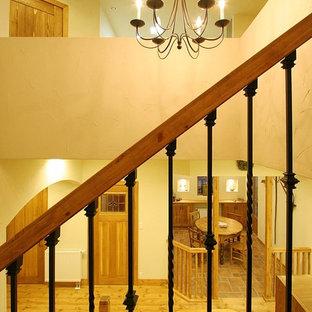 Ejemplo de escalera en U, de estilo de casa de campo, con escalones de terracota, contrahuellas de terracota y barandilla de varios materiales