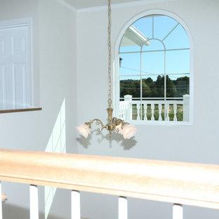 Foto de escalera en L y papel pintado, tradicional, de tamaño medio, con escalones de madera, contrahuellas de madera, barandilla de madera y papel pintado