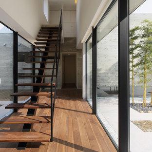 Modern inredning av en rak trappa i trä, med öppna sättsteg och räcke i metall