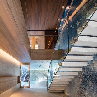 他の地域のコンクリートのコンテンポラリースタイルのおしゃれな階段 (ガラスの手すり) の写真