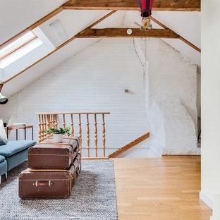Idéer för minimalistiska allrum på loftet, med vita väggar, mellanmörkt trägolv och beiget golv
