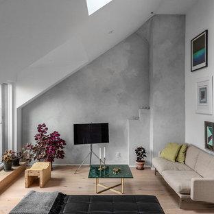 Foto på ett skandinaviskt allrum, med grå väggar, ljust trägolv och en fristående TV