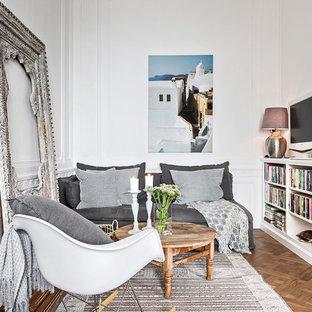 Bild på ett nordiskt avskilt allrum, med vita väggar, mellanmörkt trägolv, en fristående TV och brunt golv