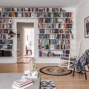Inspiration för mellanstora nordiska avskilda allrum, med ett bibliotek, vita väggar och ljust trägolv