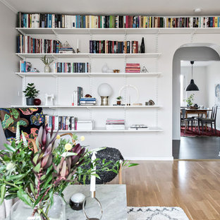 Idéer för att renovera ett skandinaviskt avskilt allrum, med ett bibliotek, beige väggar och ljust trägolv