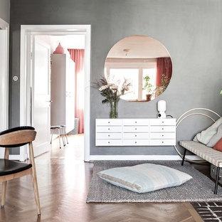 Inredning av ett minimalistiskt litet avskilt allrum, med grå väggar, mellanmörkt trägolv, en standard öppen spis, en spiselkrans i tegelsten och brunt golv