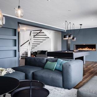 Idéer för att renovera ett stort minimalistiskt avskilt allrum, med ett spelrum, blå väggar, mörkt trägolv, brunt golv, en bred öppen spis och en väggmonterad TV