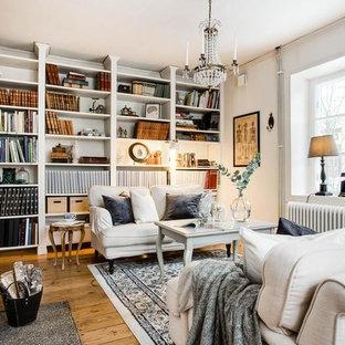 Foto på ett litet skandinaviskt avskilt allrum, med ett bibliotek, vita väggar, mellanmörkt trägolv, en öppen vedspis, en spiselkrans i gips och brunt golv