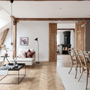 Idéer för mellanstora nordiska avskilda allrum, med vita väggar, mellanmörkt trägolv, en öppen hörnspis, en spiselkrans i trä och brunt golv
