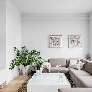 Inspiration för mellanstora skandinaviska allrum, med vita väggar, ljust trägolv och en väggmonterad TV