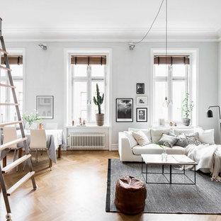 Immagine di un soggiorno scandinavo aperto e di medie dimensioni con pareti grigie, pavimento in legno massello medio e nessuna TV