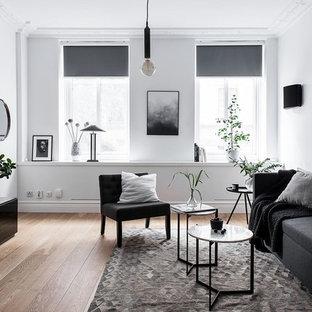 Inspiration för mellanstora nordiska allrum, med vita väggar, ljust trägolv och en väggmonterad TV