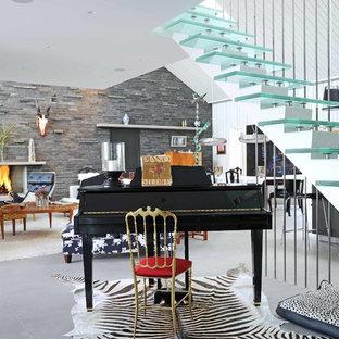 Exempel på ett eklektiskt allrum med öppen planlösning, med ett musikrum, grå väggar, klinkergolv i porslin, en standard öppen spis, en spiselkrans i sten och grått golv
