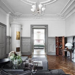 ヨーテボリの大きいヴィクトリアン調のおしゃれな独立型ファミリールーム (マルチカラーの壁、無垢フローリング、薪ストーブ) の写真