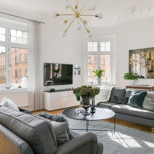 Idéer för nordiska allrum, med vita väggar, mellanmörkt trägolv och en väggmonterad TV