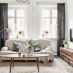 Inredning av ett skandinaviskt allrum, med vita väggar, mellanmörkt trägolv, en väggmonterad TV och brunt golv