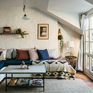 Idéer för att renovera ett mellanstort medelhavsstil avskilt allrum, med beige väggar och mellanmörkt trägolv