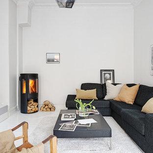 ヨーテボリの中サイズの北欧スタイルのおしゃれなファミリールーム (白い壁、塗装フローリング、壁掛け型テレビ、薪ストーブ) の写真
