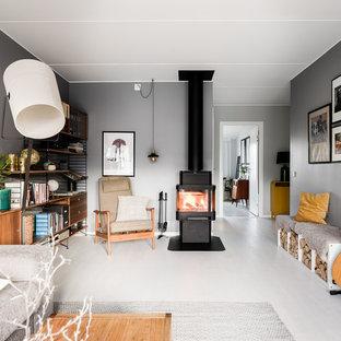 Foto på ett mellanstort nordiskt avskilt allrum, med grå väggar, laminatgolv, en öppen vedspis, en spiselkrans i metall och grått golv