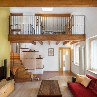 Foto på ett mellanstort medelhavsstil allrum med öppen planlösning, med flerfärgade väggar, ljust trägolv, en fristående TV och beiget golv