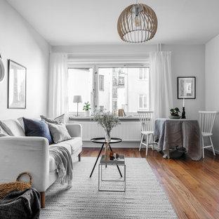Inspiration för mellanstora skandinaviska avskilda allrum, med vita väggar, mellanmörkt trägolv och brunt golv