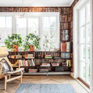 ヨーテボリの小さいトラディショナルスタイルのおしゃれな独立型ファミリールーム (ライブラリー、マルチカラーの壁、淡色無垢フローリング、テレビなし、茶色い床) の写真