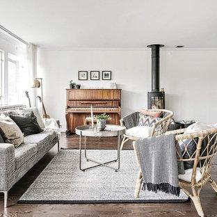 Bild på ett skandinaviskt allrum med öppen planlösning, med ett musikrum, vita väggar, mörkt trägolv, en öppen vedspis och brunt golv
