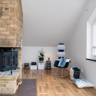 Bild på ett mellanstort minimalistiskt allrum med öppen planlösning, med vita väggar, ljust trägolv och en öppen hörnspis