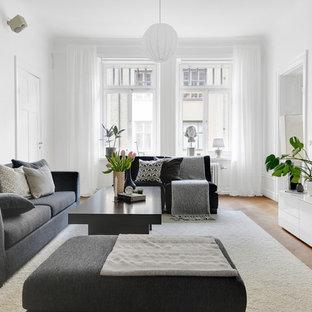 Foto på ett mellanstort skandinaviskt avskilt allrum, med vita väggar, mellanmörkt trägolv och en väggmonterad TV