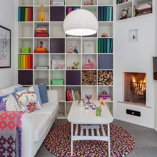 Esempio di un piccolo soggiorno minimal chiuso con libreria, pareti bianche, pavimento in cemento, TV a parete e camino ad angolo