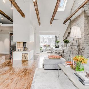 ストックホルムの中サイズのコンテンポラリースタイルのおしゃれなファミリールーム (グレーの壁、淡色無垢フローリング、テレビなし、茶色い床、薪ストーブ、コンクリートの暖炉まわり) の写真