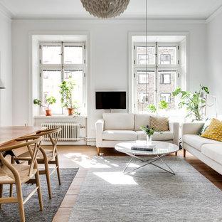 Bild på ett skandinaviskt allrum med öppen planlösning, med vita väggar, mellanmörkt trägolv, en väggmonterad TV och brunt golv