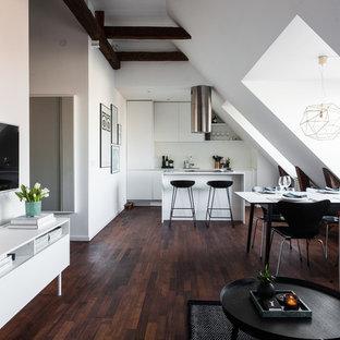 Imagen de sala de estar abierta, nórdica, de tamaño medio, sin chimenea, con paredes beige, suelo de madera oscura y televisor colgado en la pared