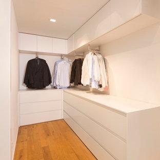 Immagine di una piccola cabina armadio per uomo moderna con pavimento in legno massello medio, ante lisce e ante bianche