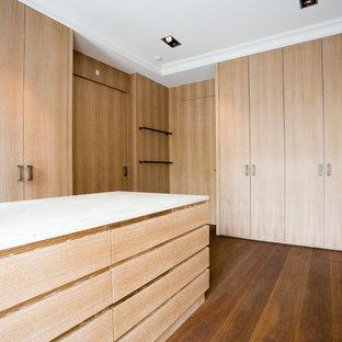Geräumiges, Neutrales Modernes Ankleidezimmer mit Ankleidebereich, flächenbündigen Schrankfronten, braunem Holzboden, braunem Boden und hellen Holzschränken in Hamburg