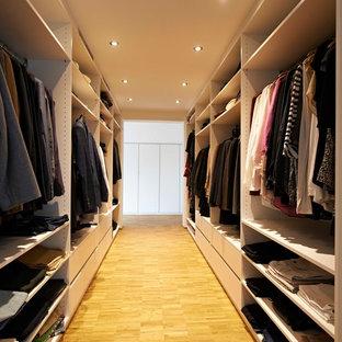 Bild på ett stort funkis walk-in-closet för könsneutrala, med öppna hyllor, bambugolv och beiget golv