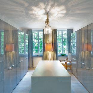 Imagen de vestidor unisex, contemporáneo, grande, con armarios con paneles lisos, puertas de armario grises, suelo de madera clara y suelo blanco