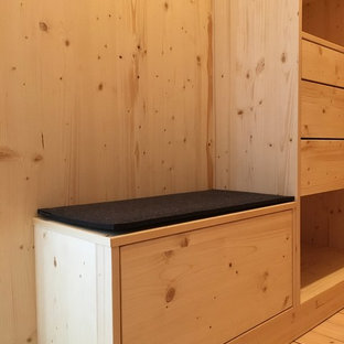 Mid-sized country walk-in wardrobe in Munich with light hardwood floors.