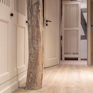 Diseño de armario y vestidor campestre, grande, con armarios con rebordes decorativos, puertas de armario grises, suelo de madera pintada y suelo gris