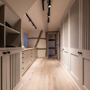 Foto de armario vestidor de mujer, de estilo de casa de campo, grande, con puertas de armario grises, suelo de madera pintada, suelo gris y armarios con rebordes decorativos