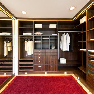 Large midcentury gender-neutral walk-in wardrobe in Stuttgart with open cabinets and beige cabinets.