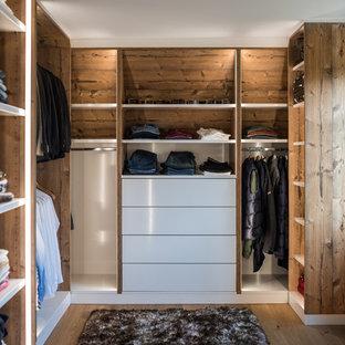 Diseño de armario vestidor de hombre, rural, de tamaño medio, con armarios abiertos, puertas de armario de madera oscura, suelo de madera en tonos medios y suelo marrón