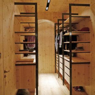 Diseño de armario vestidor unisex, moderno, de tamaño medio, con armarios abiertos, puertas de armario de madera clara, suelo de madera clara y suelo beige