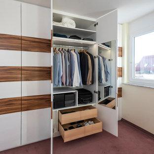 Modern inredning av ett walk-in-closet, med släta luckor, vita skåp, heltäckningsmatta och rött golv